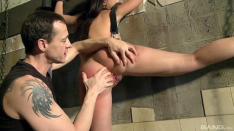 Fingering and spanking a red busty brunette in prison dungeon