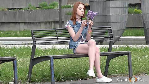 Cutie in denim outfit on a public bench outdoors Brianna admires her wild flowersr