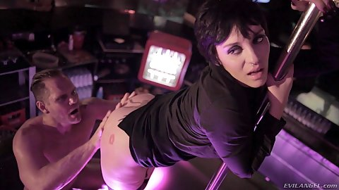 Soraya Wells holding on the strip club dancing pole while guy does things to her holes