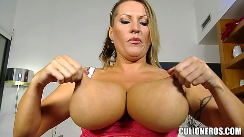Really big chested milf Laura tries to lift her really huge boobs by their nipples and then oils them