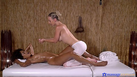 Luna Corazon and Nathaly Cherie oil massage side view on the table with one girl in yoga pants soaked in oil and havving multi finger pussy probing
