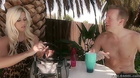 Fully clothed Jessie Volt having a drink outdoors